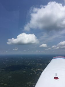 Clouds and the right wing of a Piper Warrior airplane